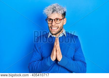 Young hispanic man with modern dyed hair wearing sweater and glasses begging and praying with hands together with hope expression on face very emotional and worried. begging.