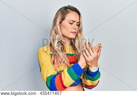 Beautiful young blonde woman wearing colored sweater suffering pain on hands and fingers, arthritis inflammation