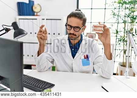 Young hispanic dentist man holding denture and toothbrush skeptic and nervous, frowning upset because of problem. negative person.
