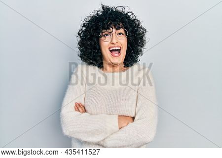 Young middle east woman with arms crossed gesture celebrating crazy and amazed for success with open eyes screaming excited.