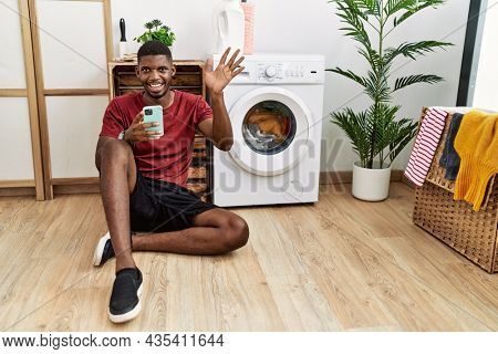 Young african american man using smartphone waiting for washing machine waiving saying hello happy and smiling, friendly welcome gesture