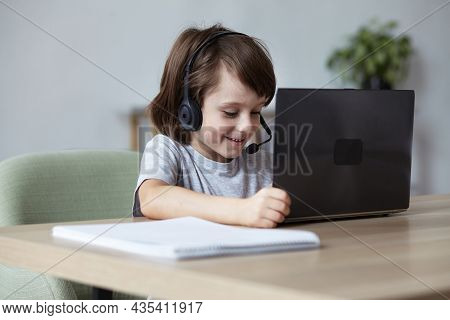Enthusiastic Cute Boy Video Chatting Merrily Using Headset And Laptop With Friends And Parents