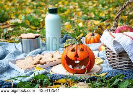 Autumn Picnic In Nature: Jack-o-lantern, Pumpkin, Tea In A Thermos, Cookies, A Basket Of Apples On A