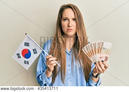 Young blonde woman holding south korea flag and won banknotes skeptic and nervous, frowning upset because of problem. negative person.