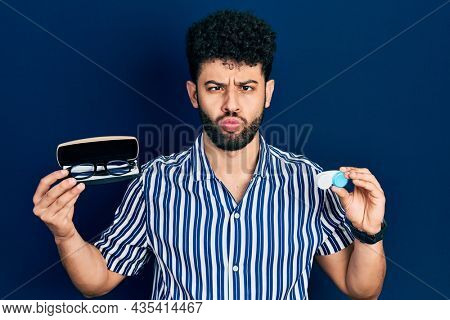 Young arab man with beard holding glasses and contact lenses making fish face with mouth and squinting eyes and comical.