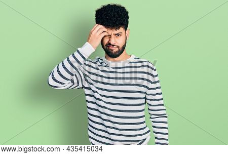 Young arab man with beard wearing casual striped sweater worried and stressed about a problem with hand on forehead, nervous and anxious for crisis