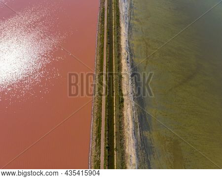 Aerial Drone Shot Of A Dam With Asphalt Road Between Estuaries With Different Color Of Water. Pink O