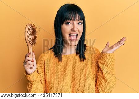 Young hispanic woman holding comb loosing hair celebrating victory with happy smile and winner expression with raised hands