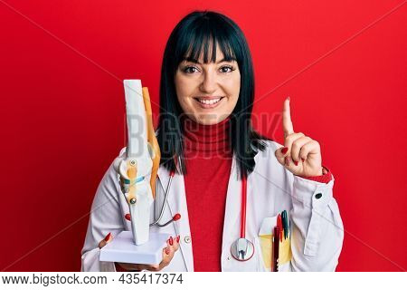 Young hispanic doctor woman holding anatomical model of knee joint smiling with an idea or question pointing finger with happy face, number one