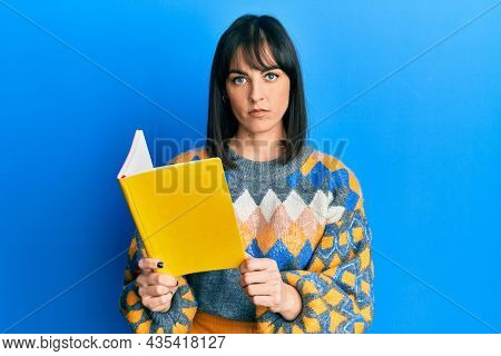 Young hispanic woman reading book thinking attitude and sober expression looking self confident