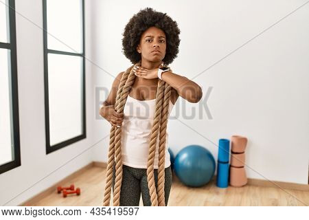 Young african american woman with afro hair at the gym training with battle ropes cutting throat with hand as knife, threaten aggression with furious violence