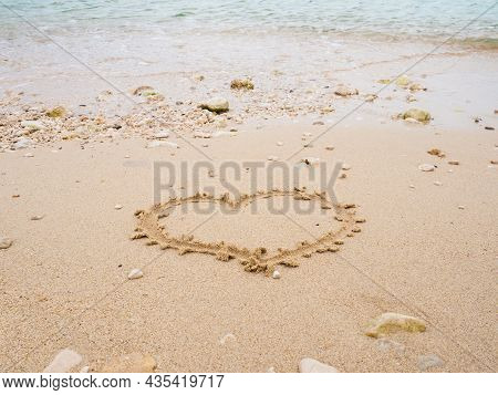 Hand Writing Heart Shape On The Beach In Sand By The Sea