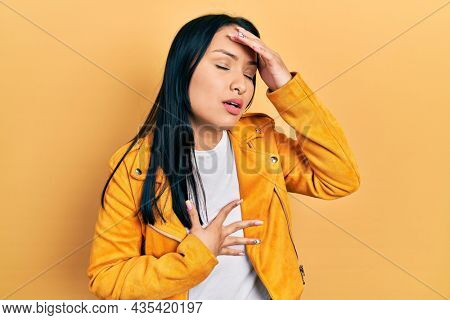 Beautiful hispanic woman with nose piercing wearing yellow leather jacket touching forehead for illness and fever, flu and cold, virus sick