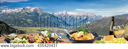 Panorama Of Tauer Alps With Traditional Austrian Specialties Such As Steaks, Fries, Potatoes, A Bott