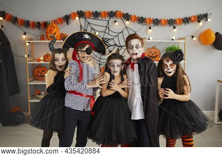 Portrait Of Group Of Children In Creative Costumes With Scared Faces At Halloween Party.