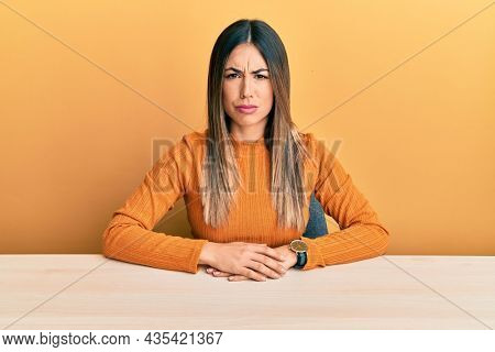 Young hispanic woman wearing casual clothes sitting on the table skeptic and nervous, frowning upset because of problem. negative person.