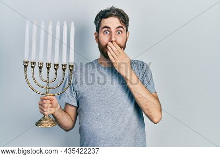 Caucasian man with beard holding menorah hanukkah jewish candle covering mouth with hand, shocked and afraid for mistake. surprised expression