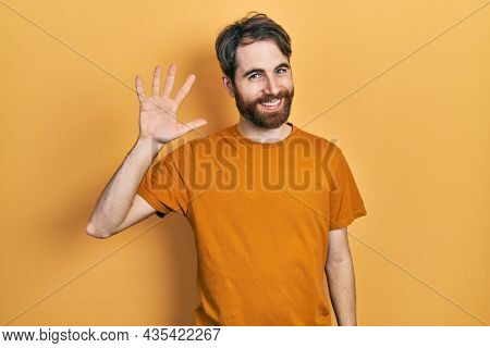 Caucasian man with beard wearing casual yellow t shirt waiving saying hello happy and smiling, friendly welcome gesture