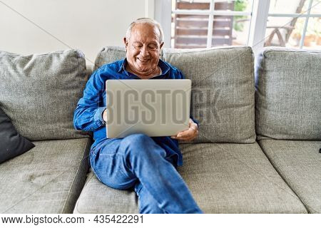 Senior man with grey hair sitting on the sofa at the living room of his house using computer laptop