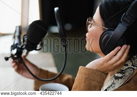Asian Radio Host In Glasses And Headphones Touching Scissor Arm With Mic During Podcast