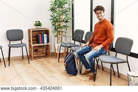 Young hispanic man smiling confident sitting on chair at waiting room