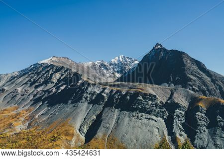 Scenic Alpine Landscape With Sharp Rocky Pinnacle And Snow-covered Mountain In Sunlight In Autumn. M