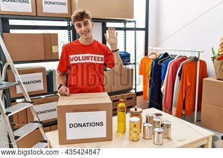 Young caucasian man volunteer holding donations box waiving saying hello happy and smiling, friendly welcome gesture
