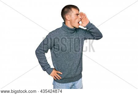 Young blond man wearing casual clothes shouting and screaming loud to side with hand on mouth. communication concept.