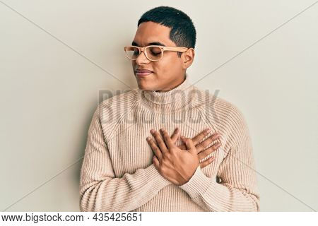 Young handsome hispanic man wearing turtleneck neck sweater and glasses smiling with hands on chest, eyes closed with grateful gesture on face. health concept.