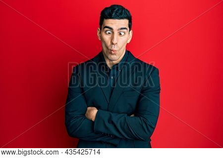 Handsome hispanic business man with arms crossed gesture making fish face with mouth and squinting eyes, crazy and comical.