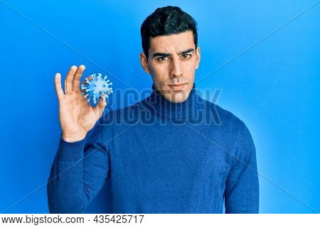 Handsome hispanic man holding virus toy thinking attitude and sober expression looking self confident