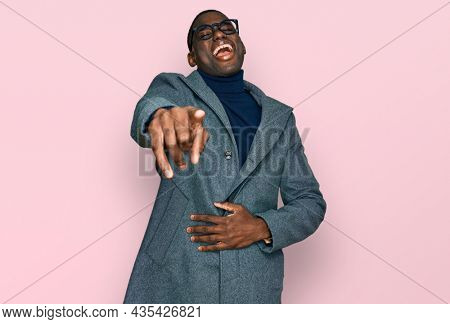 Young african american man wearing business clothes and glasses laughing at you, pointing finger to the camera with hand over body, shame expression