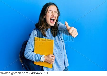 Young brunette student woman wearing student backpack doing thumbs up gesture angry and mad screaming frustrated and furious, shouting with anger looking up.