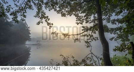 Quiet And Foggy Lake At Dawn. Tree Branches With Leaves In The Foreground. A Serene Lake Landscape I