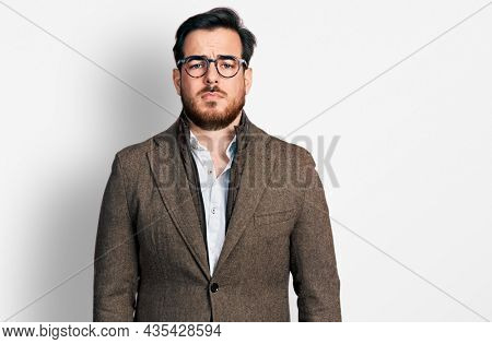 Young hispanic man wearing business jacket and glasses depressed and worry for distress, crying angry and afraid. sad expression.