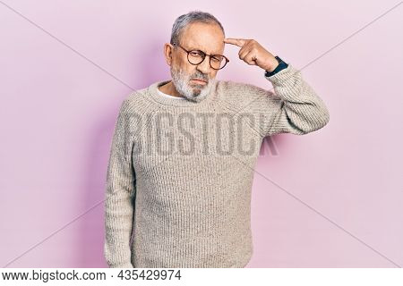 Handsome senior man with beard wearing casual sweater and glasses pointing unhappy to pimple on forehead, ugly infection of blackhead. acne and skin problem