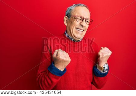 Handsome senior man with grey hair wearing casual clothes and glasses excited for success with arms raised and eyes closed celebrating victory smiling. winner concept.