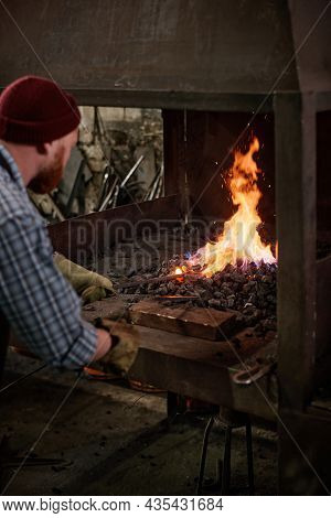 Rear View Of Manual Worker Putting Coal Into Furnace In The Workshop