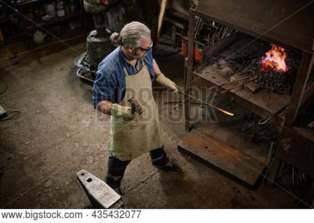 Mature Blacksmith In Protective Wear Adding Coals In Furnace And Burning The Flame In The Blacksmith