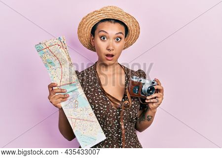 Beautiful hispanic woman with short hair holding city map and vintage camera in shock face, looking skeptical and sarcastic, surprised with open mouth