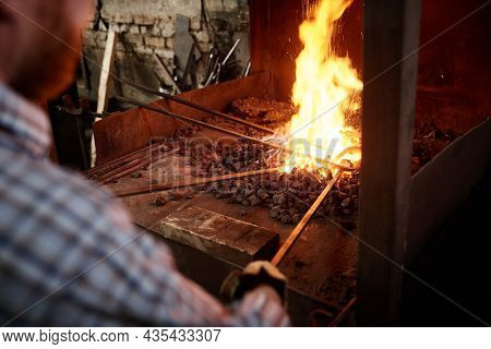 Close-up Of Blacksmiths Holding Metallic Sticks And Heating Them With Fire In The Furnace