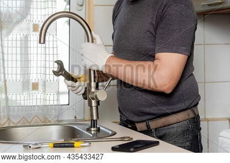 A Plumber In The Kitchen Installs A New Water Tap. Repair Of The Faucet In The Kitchen Near The Sink