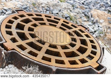 Cast-iron Manhole Of The Storm Sewer System On The Road In Front Of The Asphalt Pavement