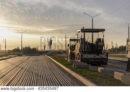 Road Repair And Asphalt Paving With A Specialized Machine In The Evening Against The Backdrop Of The