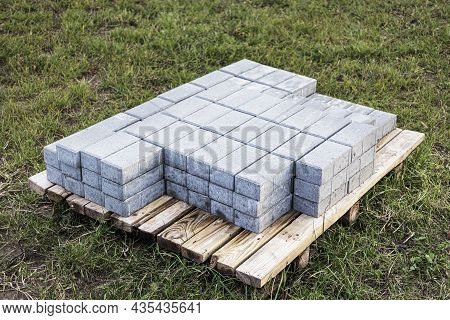 Paving Slabs On A Pallet Prepared For Installation On A Green Lawn. Paving The Road With Concrete Pa