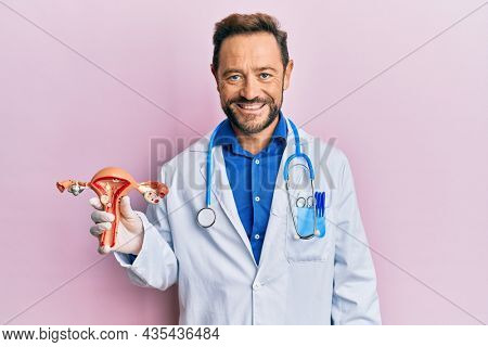 Middle age gynecologist man holding anatomical model of female genital organ looking positive and happy standing and smiling with a confident smile showing teeth