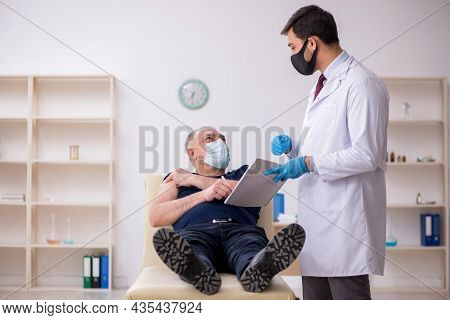 Old male patient visiting young male doctor in vaccination conce