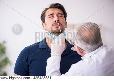 Young male patient visiting old male doctor during pandemic