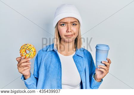 Beautiful blonde woman eating doughnut and drinking coffee skeptic and nervous, frowning upset because of problem. negative person.