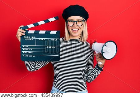 Beautiful blonde woman holding video film clapboard and megaphone winking looking at the camera with sexy expression, cheerful and happy face.